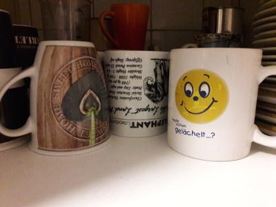 freundliche Tassen im Schrank