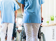 Pflegepersonal das Rollstühle schiebt
