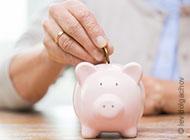 Ältere Frau wirft Münze in ein Sparschwein