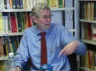 Prof. Dr. Hans Jürgen Schlösser sitzt vor einem Bücherregal