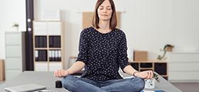 Frau macht Yoga auf dem Schreibtisch