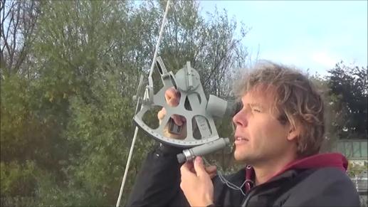 """Christian Sauerbeck sitzt an Deck unserer Segelyacht """"Helgoland Express"""", die in Finkenwerder am Steg liegt. Im Hintergrund sieht man die Bäume und die Böschung am Ufer der Elbe. Christian hält den Sextanten vor den Augen, um damit einen Höhenwinkel zu messen."""