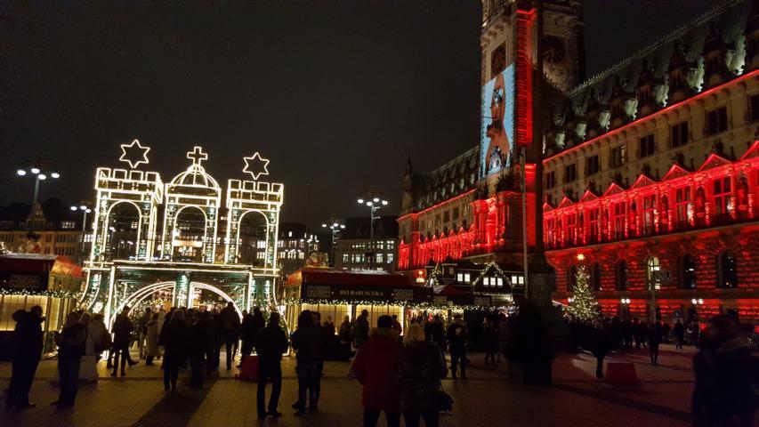 Der weihnachtlich erleuchtete Weihnachtsmarkt auf dem Hamburger Rathausplatz und das rot angestrahlte Rathaus.