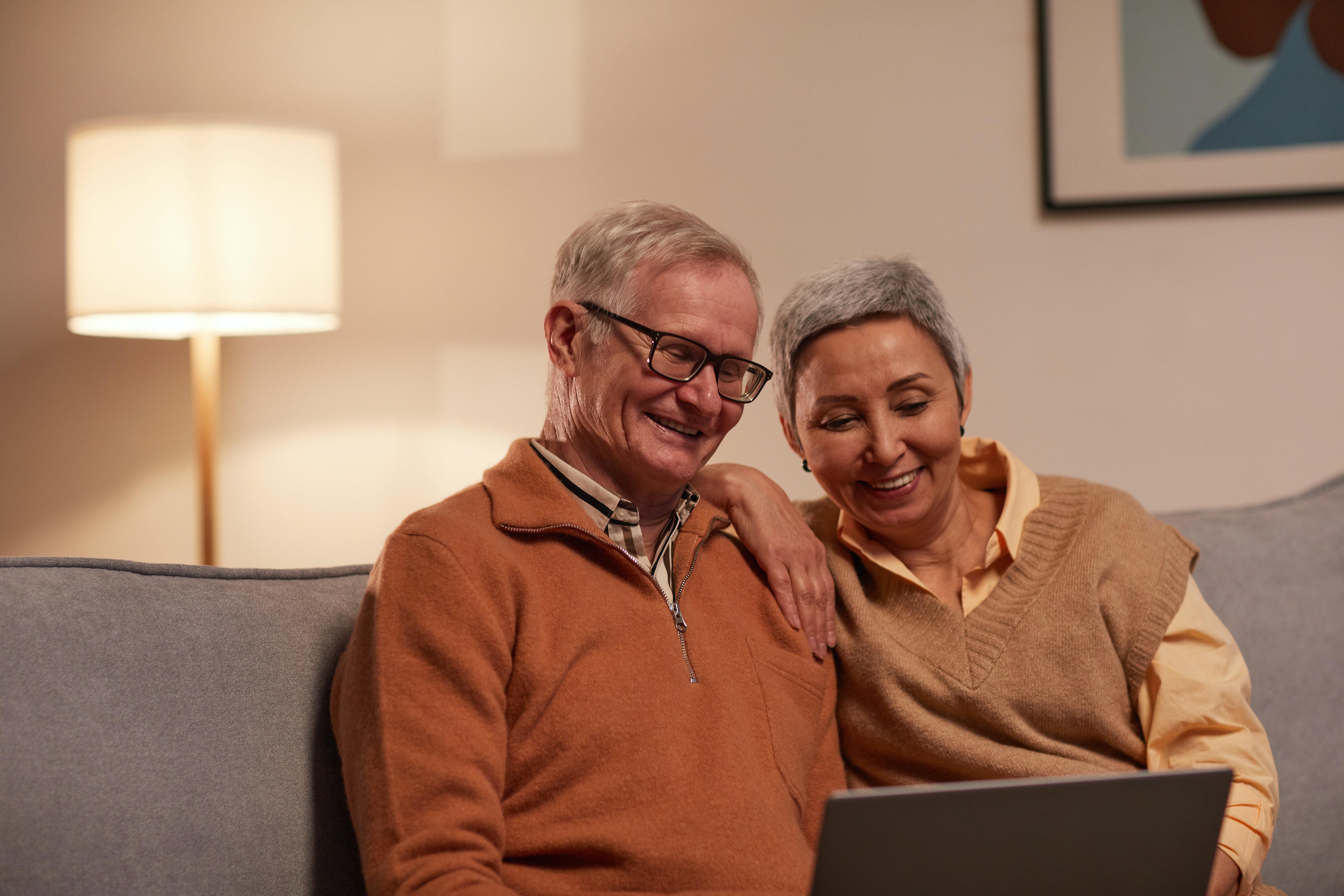 Ein älterer Mann und eine ältere Frau sitzen auf dem Sofa und blicken gemeinsam in einen Laptop