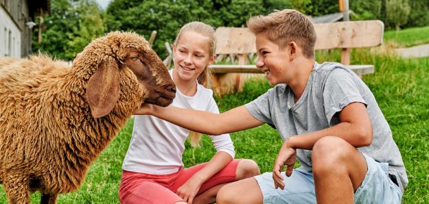 Foto eines circa 10-jährigen, lächelnden Mädchens und Bubens, die in der Hocke vor einem braunen Schaf sitzen und es streicheln