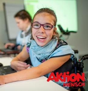 Foto eines lächelnden ca. 12-jährigen Mädchens mit Brille im Rollstuhl, die an einem Laptop sitzt