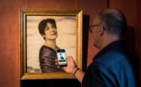 Foto eines älteren Herren mit Glatze und Brille von schräg hinten, der in einem Museum sein Smartphone auf ein Gemälde richtet