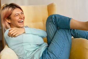Eine Frau sitzt auf einem Sofa und lacht