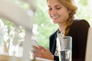 Eine Frau schaut auf ihr Smartphone mit der Daimler BKK App