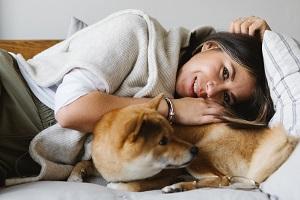 Eine Frau liegt auf dem Sofa mit einem Hund