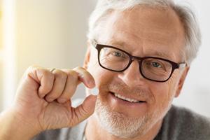 Ein älterer Herr mit einer Tablette in der Hand