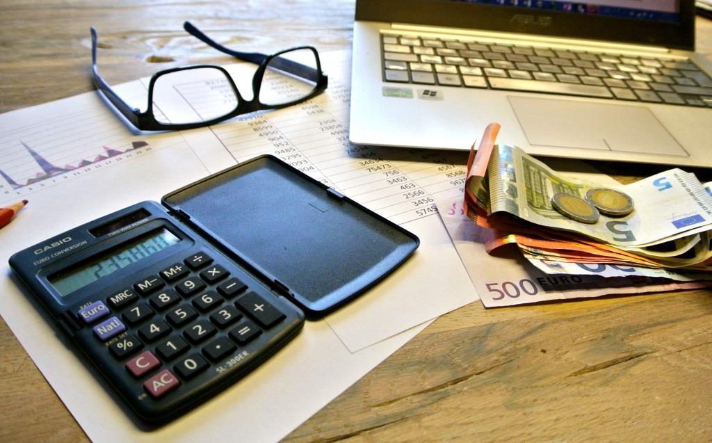 Taschenrechner und Geld liegen auf Schreibtisch