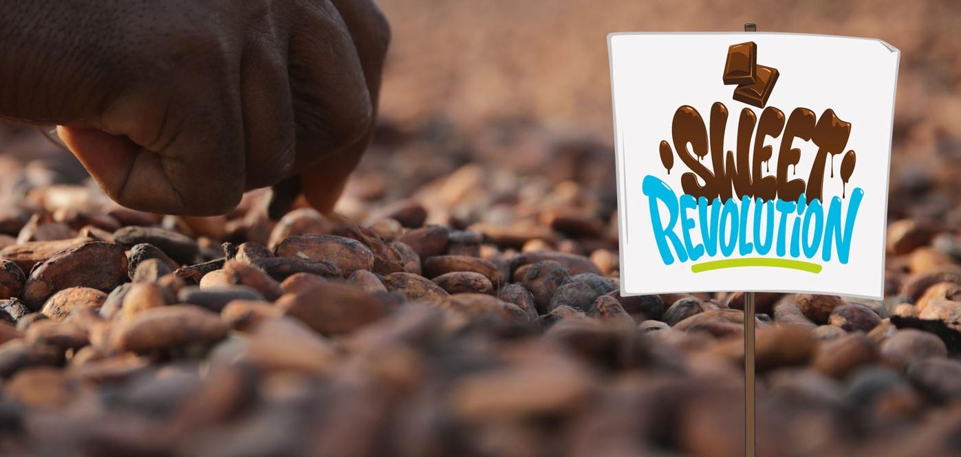"""Protest-Plakat im  Comic-Stil mit der Aufschrift """"Sweet Revolution"""" vor Hintergrund aus Kakaobohnen"""