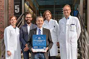 Foto (UKM/Deiters): Gemeinschaftliche Auszeichnung für hohe Hygienestandards: (v.l.) Prof. Stefanie Kampmeier, Udo Kogge und Prof. Alexander Mellmann (alle Institut für Hygiene) sowie Dr. Dagmar Horn und Dr. Christian Lanckohr vom ABS-Team.
