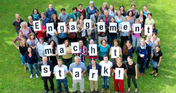 Auf dem Bild sind viele Menschen zu sehen, die Karten mit einer Botschaft in der Hand halten