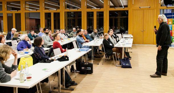 Auf dem Foto sind Menshcen zu sehen, die sitzen und einen Mann vorne, der ein Mikrofon hält