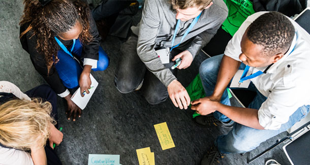 The photo is taken from a bird's eye view. Five people are sitting on the floor. Index cards with writing on them lie between the people.