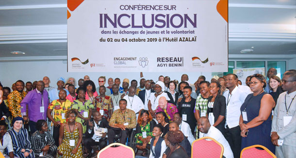 The photo shows a group of around 40 people all looking into the camera. They are standing under a banner with the inscription 'conference for inclusion in youth exchange programmes and volunteering'.