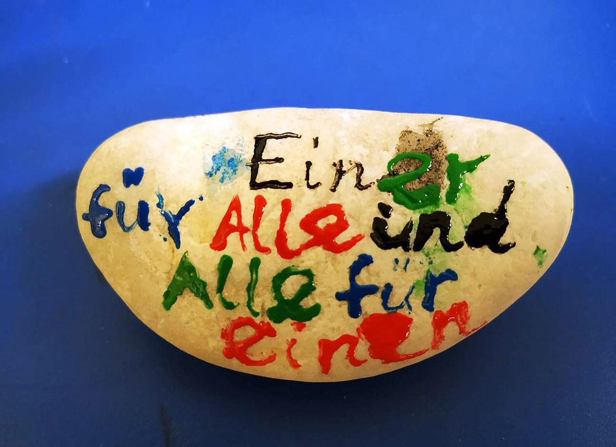 """Stein mit Aufschrift """"Einer für alle und Alle für Einen"""". Quelle: weltinderschule.uni-bremen.de"""
