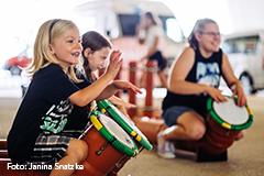 Fröhliche Kinder trommeln gemeinsam auf Abwasserrohr-Trommeln.