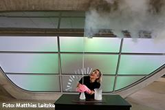 Eine Showmasterin begeistert das Publikum mit Experimenten.