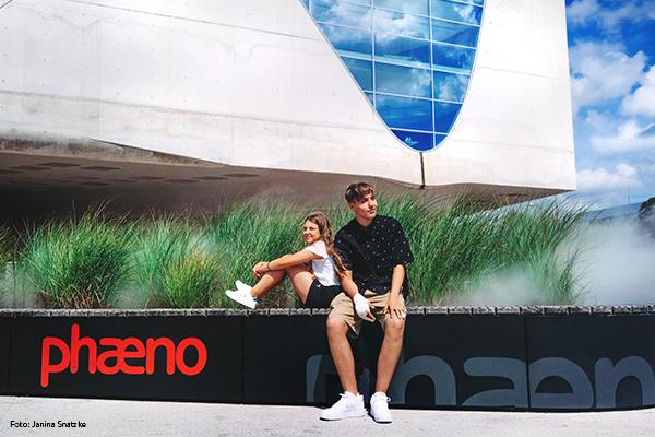 Zwei Jugendliche sitzen auf einer Bank vor dem phaeno und genießen das Sommerfeeling.