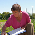 Frau arbeitet auf dem Feld mit Klemmbrett