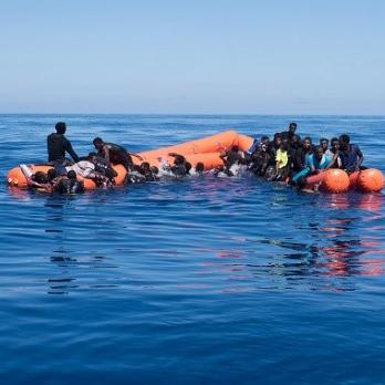 Flüchtlinge warten auf einem kaputten Schlauchboot im Mittelmeer auf Hilfe