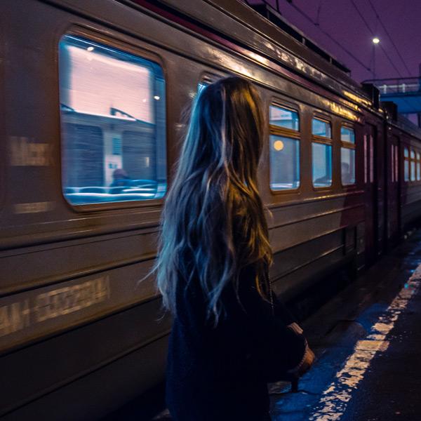 Eine Frau mit langen Haaren, von hinten zu sehen, steht vor einem einfahrenden Zug. Es ist dunkel, der Himmel schimmert etwas lila.