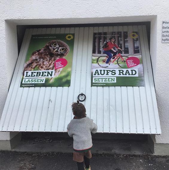 """Ein Garagentor mit 2 Wahlplakaten der Grünen zur Kommunalwahl 2020. Auf den Plakaten steht """"Leben lassen"""" und """"Aufs Rad setzen"""". Ein Kind öffnet gerade das Tor."""