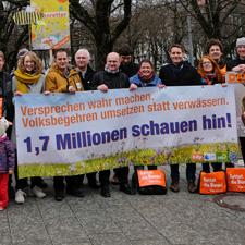 """Gruppenfoto des breiten Bündnisses für das """"Volksbegehren Artenvielfalt"""" ein Jahr nach dem großen Erfolg vor der bayerischen Staatskanzlei mit einem Banner und der Aufschrift """"Versprechen wahr machen, Volksbegehren umsetzen statt verwässern: 1,7 Millionen schauen hin!"""""""