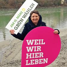 """Steffi König in Rosenheim mit dem Pin in der Hand, auf dem steht """"Weil wir hier leben"""""""