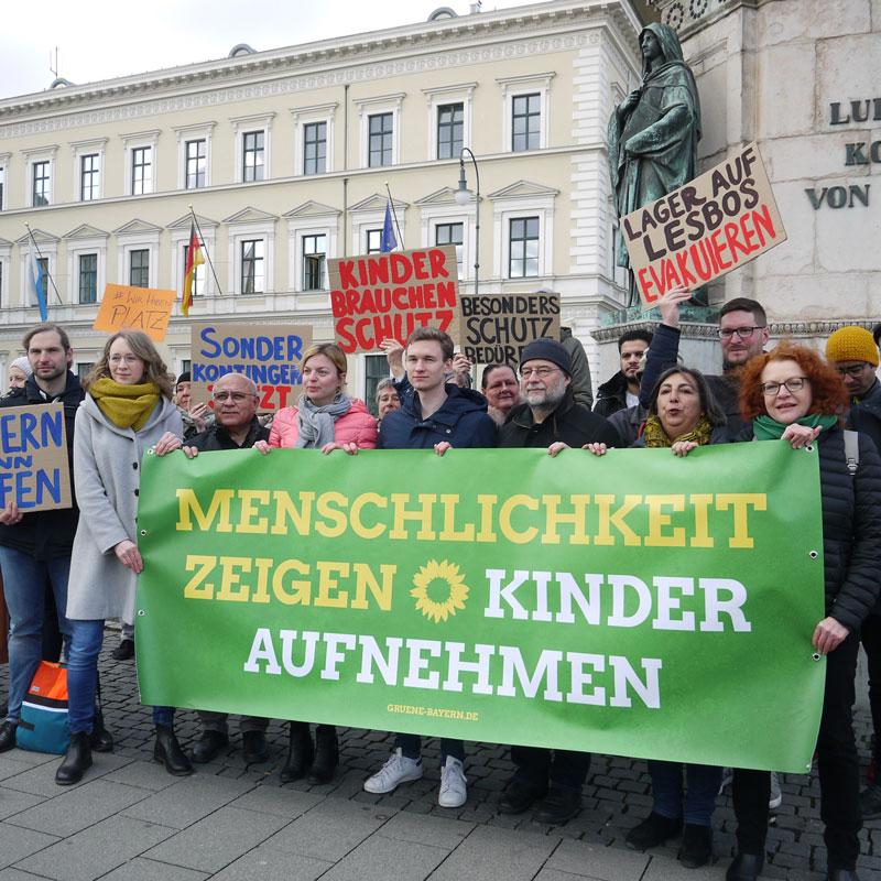 """Gruppenfoto bei der Protestaktion für ein bayerisches Sofortaufnahmeprogramm für die Geflüchteten auf Lesbos, es wird ein Banner gespannt, auf dem steht: """"Menschlichkeit zeigen, Kinder aufnehmen"""""""