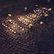 """Bei der Mahnwache für die Opfer von Hanau in München: Auf dem Boden sind Teelichter so angeordnet, dass der Schriftzug """"Hanau"""" entsteht, daneben liegen weiße Rosen"""
