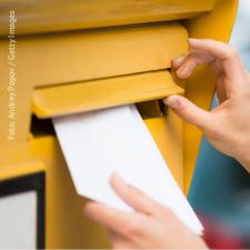 Nahaufnahme eines Umschlags, der gerade in einen gelben Briefkasten geworfen wird
