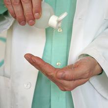 Nahaufnahme der Hände eines Arztes, der gerade Desinfektionsmittel aufträgt