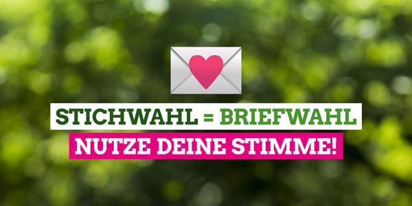 """Das Liebesbrief-Emoji vor verschwommenem grünem Hintergrund, darauf der Text """"Stichwahl = Briefwahl. Nutze deine Stimme!"""""""