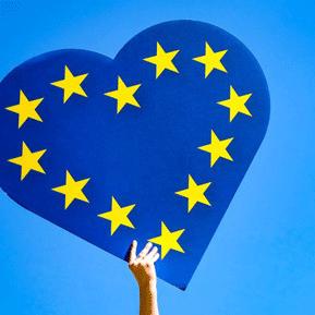 Ein blaues Herz mit gelben Europasternen darauf wird von einer Hand in die Luft gehalten