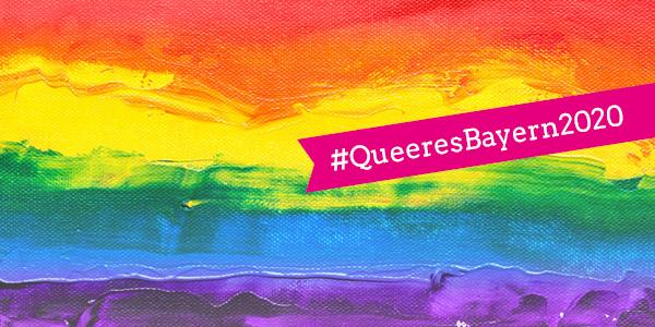 Ein gemalter Regenbogen-Farbverlauf, darauf ein pinkes Fähnchen mit dem Hashtag #QueeresBayern2020
