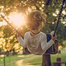 Foto eines schaukelnden Kindes an einem sonnigen Sommerabend