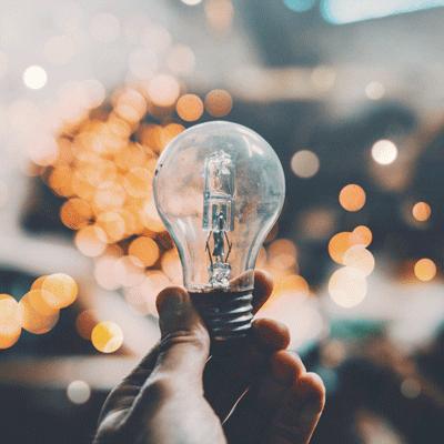 Eine Hand hält eine Glühbirne. Im Hintergrund sind schemenhaft weitere Lichtflecken zu erkennen.