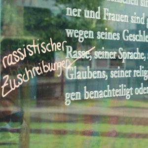 """Ein Ausschnitt des Textes des Grundgesetzes auf einer Glasscheibe. Das Wort """"Rasse"""" ist durchgestrichen und durch """"rassistischer Zuschreibungen"""" ersetzt"""