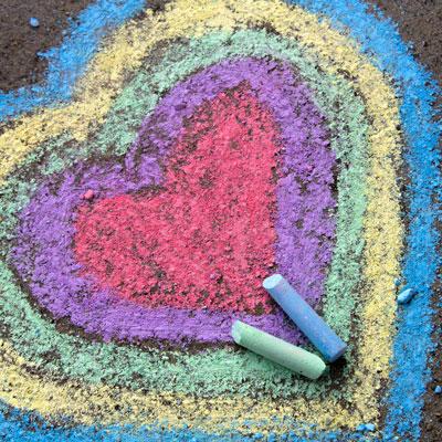 Ein Herz aus bunter Kreide auf einen Teerboden gemalt