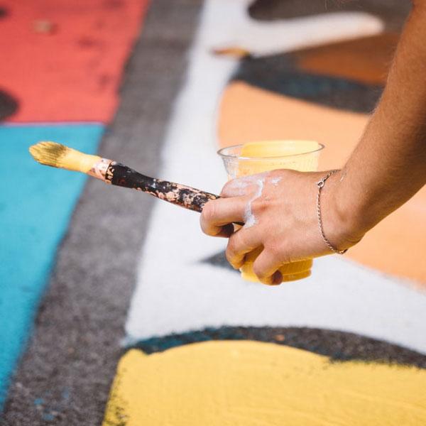 Ein Hand, die einen mit Farbe befüllten Pinsel hält, in Nahaufnahme vor einem bemalten Boden