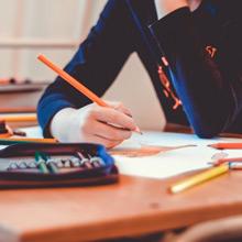 Ein Schulkind beim Malen mit Buntstiften, Nahaufnahme der Hände und des Federmäppchens