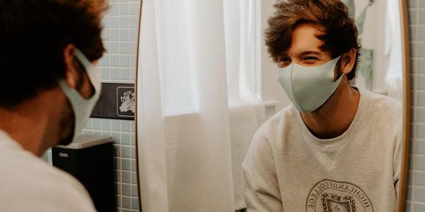 Ein junger Mann mit Mund-Nasen-Schutz schaut sich während des Händewaschens lachend im Spiegel an