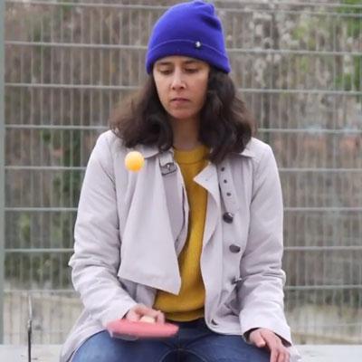 Eine junge Frau spielt alleine Tischtennis