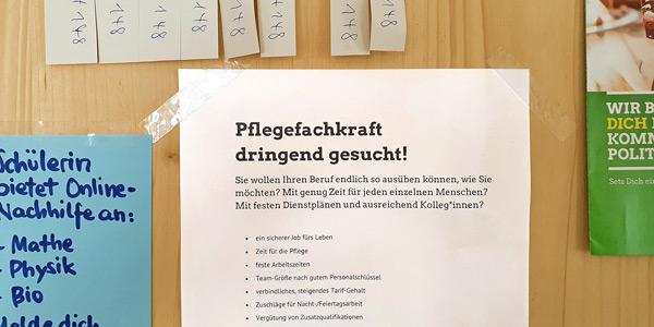 """Eine mit Plakaten vollgeklebte Wand, im Fokus eine Stellenanzeige mit dem Titel """"Pflegefachkraft dringend gesucht!"""""""