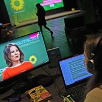 Szene aus dem Studio des digitalen Politischen Aschermittwochs der bayerischen GRÜNEN: Auf einem Bildschirm läuft gerade die Rede der Bundesvorsitzenden Annalena Baerbock