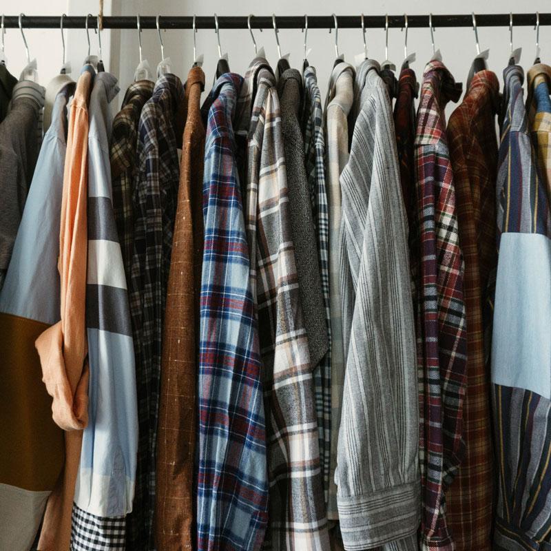 Einige Kleidungsstücke hängen an einer Kleiderstange